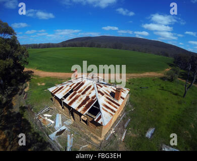Aerial view of dilapidated historic cottage next to green wheat field, near Moora, Wheatbelt region, Western Australia - Stock Photo