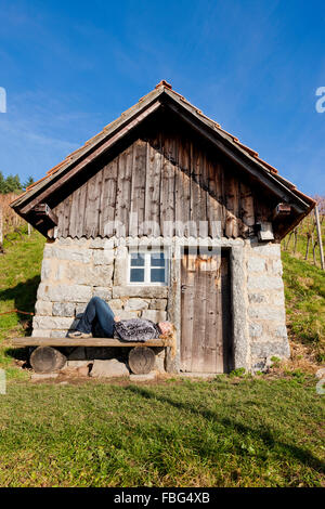 Woman basks in front of a small house - Stock Photo