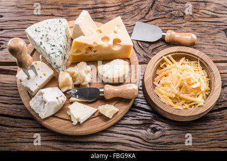 Variety of cheeses on a wooden board. - Stock Photo
