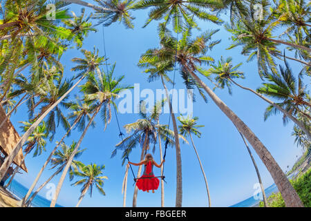 Beautiful girl flying high with a fun in blue sky on the rope swing among coconut palms on sea beach in tropical - Stock Photo