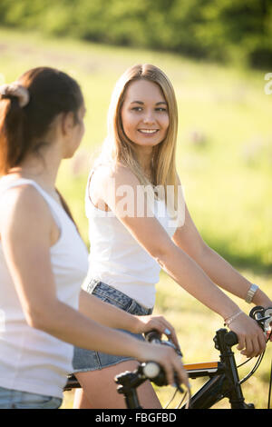 Two young beautiful cheerful women girlfriends wearing jeans shorts on bicycles in park on sunny summer day, having - Stock Photo