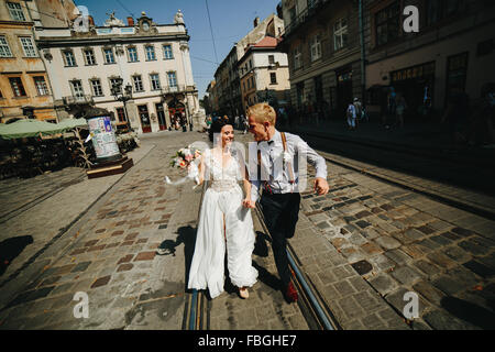 the bride and groom running along streets - Stock Photo