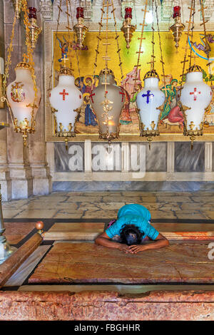 Prayer at Stone of Anointing at the entrance to the Church of the Holy Sepulchre in Jerusalem. - Stock Photo