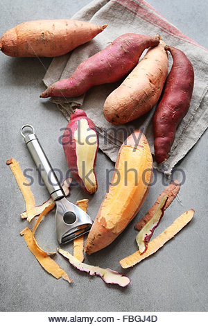 Orange and red japanese  sweet potatoes on grey background - Stock Photo