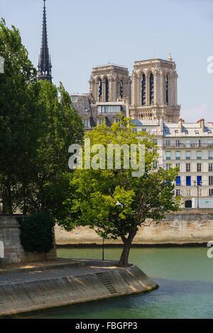 Tip of Ile Saint Louis with towers and spire of Notre Dame de Paris Cathedral on Ile de la Cite, along the Seine - Stock Photo