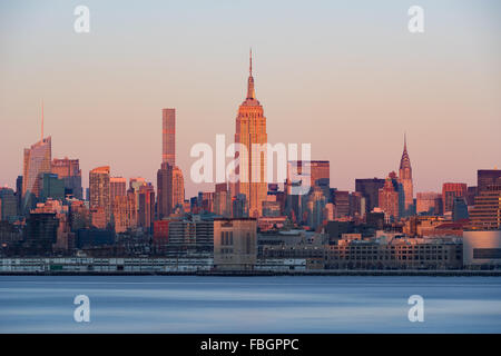 New York City Midtown Manhattan skyscrapers at sunset from across the Hudson River. At center, the Empire State - Stock Photo