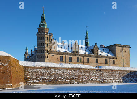 The snow-covered Kronborg Castle in Elsinore, Helsingør, on a sunny winter's day, frozen moat and a blue sky. - Stock Photo