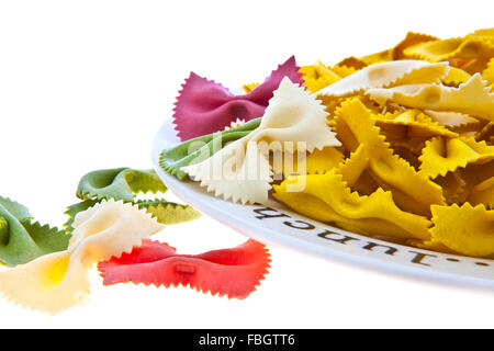 Uncooked rainbow farfalle pasta spilling from plate on white background with copy space. - Stock Photo