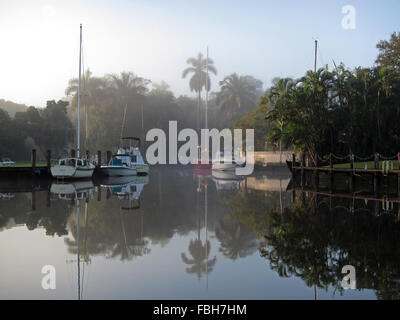 Foggy sunrise amidst yachts on New River, Fort Lauderdale, Florida - Stock Photo