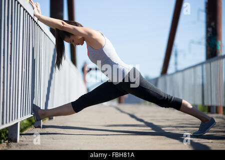 young girl doing splits while warming up at ballet dance