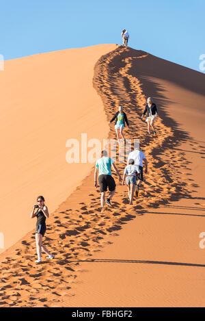 Tourists climbing sand dune, Sossusvlei, Namib Desert, Namib-Naukluft Park, Hardap Region, Republic of Namibia - Stock Photo