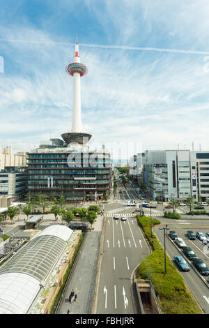 Sunny blue sky with Kyoto Tower and nearby city buildings and neat streets in front of Kyoto Station in Japan. Copy - Stock Photo