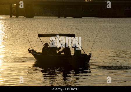 Three silhouetted men and one woman going fishing in a small runabout metal boat - Stock Photo