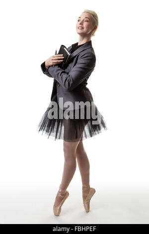 woman holding a filofax, wearing a tutu and a suit jacket, toes en pointe - Stock Photo