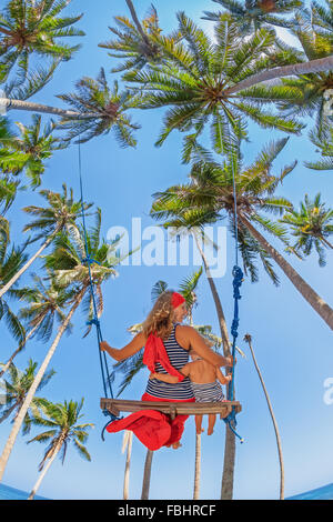 Mother with baby girl fly high with fun in sky on the rope swing among coconut palms on the sea beach on tropical - Stock Photo