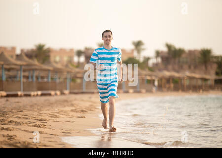 Healthy lifestyle: handsome young man working out outdoor, running through the surf on the sand shore of tropical - Stock Photo