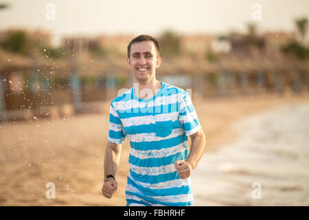 Healthy lifestyle: handsome cheerful young man having fun running with splashes through the surf on the sand shore - Stock Photo