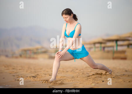 Healthy lifestyle: young fitness girl working out outdoors, doing lunge warming up exercises before running practice - Stock Photo