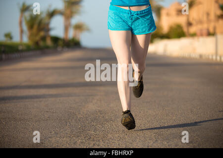 Healthy lifestyle: close up of young woman legs in running shoes jogging on fast speed outdoors on the sunny summer - Stock Photo