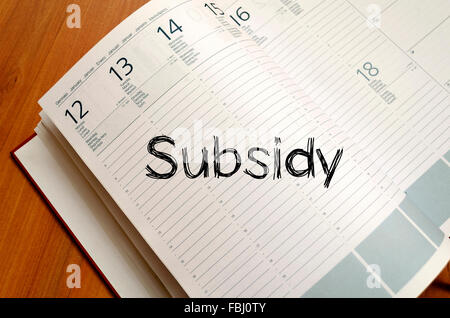 Subsidy text concept write on notebook with pen - Stock Photo