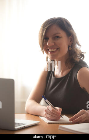 Friendly smiling young female sitting in front of laptop, student or office woman in formal wear writing notes, - Stock Photo