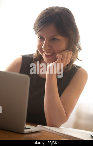 Friendly smiling young woman in formal wear using laptop, typing, working on computer, surfing internet - Stock Photo