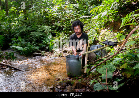 Native people taking water from a small creek in the middle of tropical rainforest in Batang Toru, North Sumatra, Indonesia.