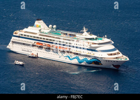 Santorini in Aegean Sea. Ocean-going luxury cruise ship, Aida Cara, seen from above, sailing on very calm sea, one - Stock Photo