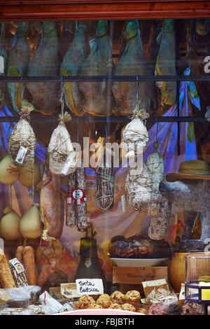 Ham, sausage, cheese, regional specialities, lined up, hanging in the shop-window, view into shop. Tuscany, Italy - Stock Photo
