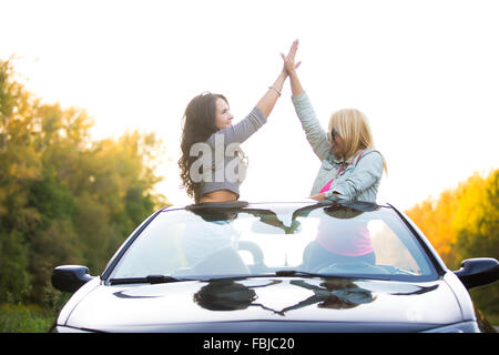Two happy friends driving modern luxury cabriolet car on vacation on summer day. Beautiful cheerful young ladies - Stock Photo