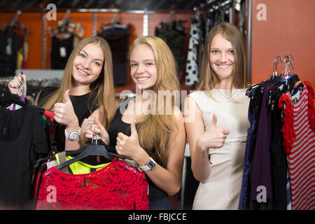 Portrait of teen girlfriends posing with new clothes. Group of three happy smiling young beautiful women shopping - Stock Photo