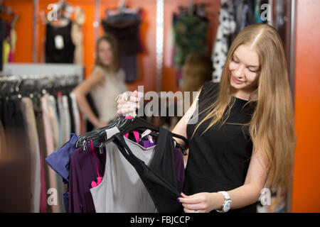 Smiling young beautiful woman shopping, going to fitting room in fashion mall, carrying new clothes. Pretty model - Stock Photo