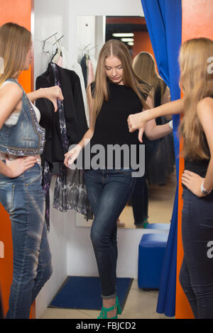 Group of three girlfriends shopping together. Young beautiful woman wearing jeans standing in fitting room in mall - Stock Photo