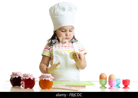Child little chef with flour stretching the dough - Stock Photo