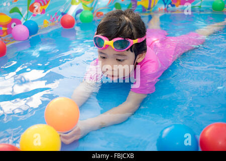 A baby girl in pink suit playing water and balls in blue kiddie pool - Stock Photo