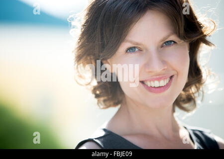 Headshot portrait of happy beautiful caucasian woman on the street in summer, friendly smiling, looking at camera - Stock Photo