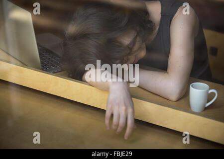 Young woman lying on her arms on the table in cafe in front of laptop with cup of coffee, sleepy, tired, overworked - Stock Photo