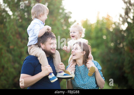 Portrait of happy beautiful family of four walking in park in summer. Mom and dad carrying two little cheerful laughing - Stock Photo
