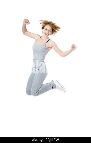 Portrait of young happy smiling slim sporty beautiful woman wearing grey sportswear, jumping with joy, isolated - Stock Photo