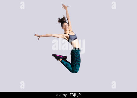 One happy attractive gorgeous young fit modern woman in aquamarine sportswear with ponytail working out, dancing, - Stock Photo