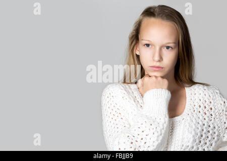 Portrait of beautiful focused pensive casual caucasian teenage girl wearing white knitted sweater, studio image, - Stock Photo