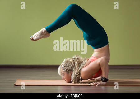 Sporty beautiful blond young woman in sportswear working out indoors, doing handstand, yoga Scorpion Posture, Vrischikasana - Stock Photo