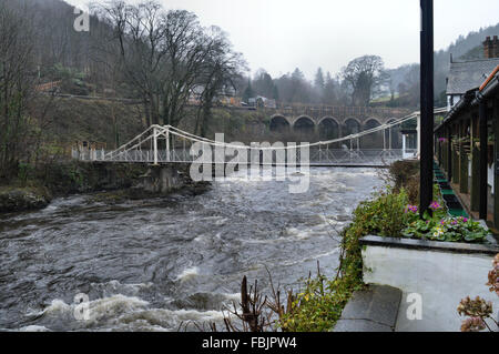 River Dee and two people crossing the chain foot bridge adjoining the Chainbridge Hotel Llangollen - Stock Photo