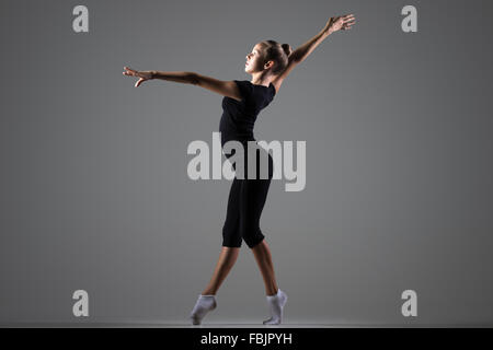 Beautiful cool young fit gymnast athlete woman in sportswear working out, dancing on tiptoes, doing art gymnastics - Stock Photo