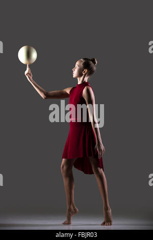 Beautiful cool young fit gymnast athlete woman in sportswear red dress working out, doing rhythmic gymnastics exercise - Stock Photo
