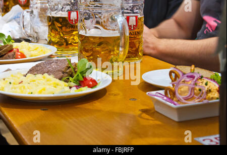 Plates of food and mugs of beer on a table in a beer hall at Oktoberfest in Munich, Germany. - Stock Photo