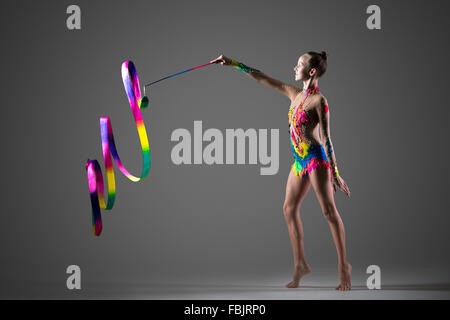 Beautiful happy cool young fit gymnast athlete woman in colorful sportswear working out, doing rhythmic gymnastics - Stock Photo