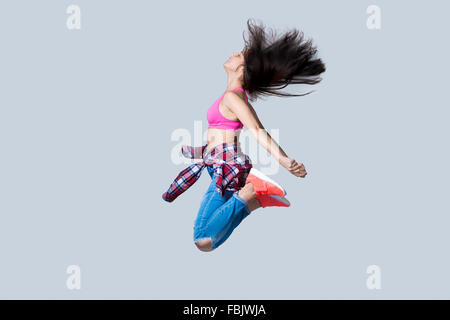 Beautiful young happy smiling fit modern hip-hop dancer woman working out wearing jeans, jumping, studio, gray background - Stock Photo