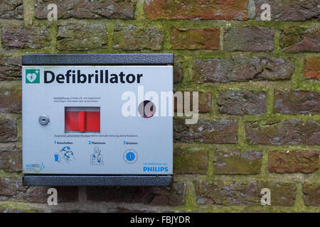 A defibrillator mounted on a wall in Germany - Stock Photo
