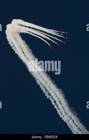 Red Arrows in formation against a vivid blue sky with white smoke at RIAT 2015 air show - Stock Photo